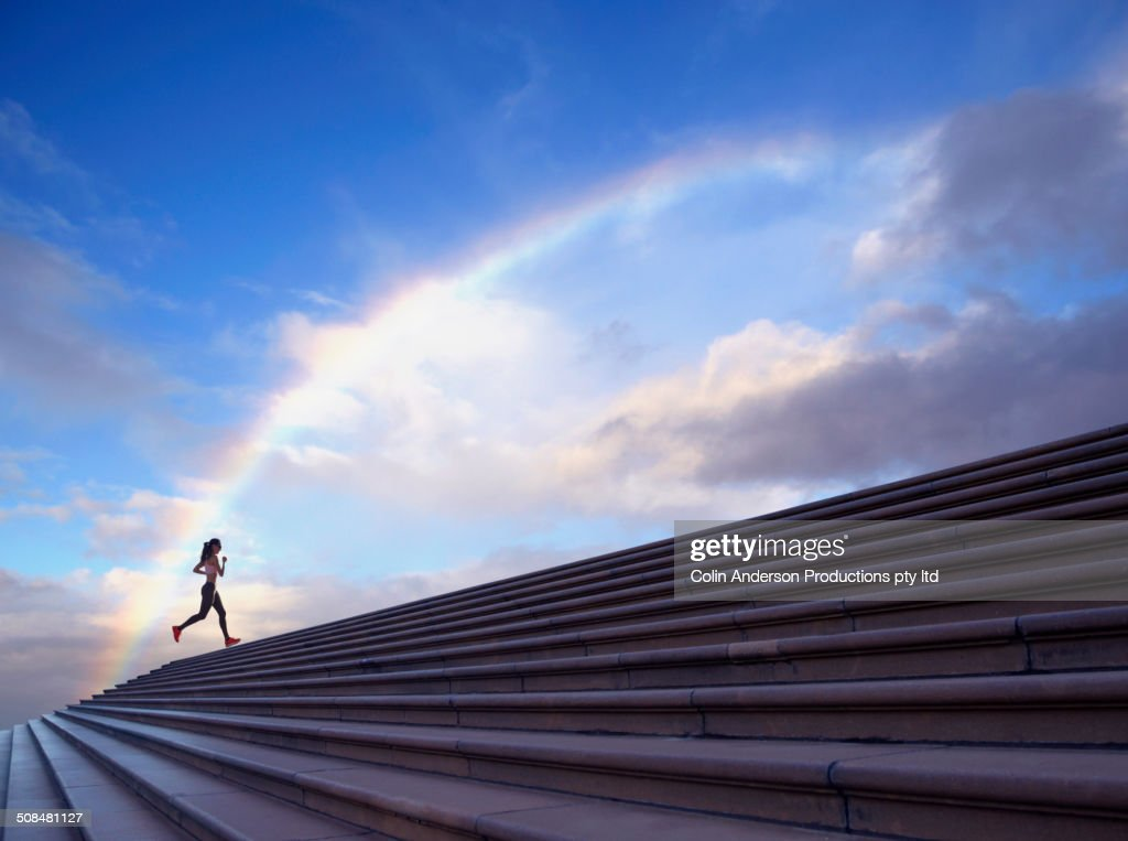 Pacific Islander woman jogging on concrete steps