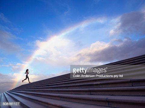 Pacific Islander woman jogging on concrete steps