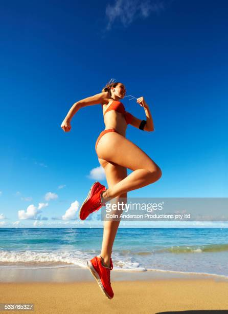 Pacific Islander woman jumping for joy on beach