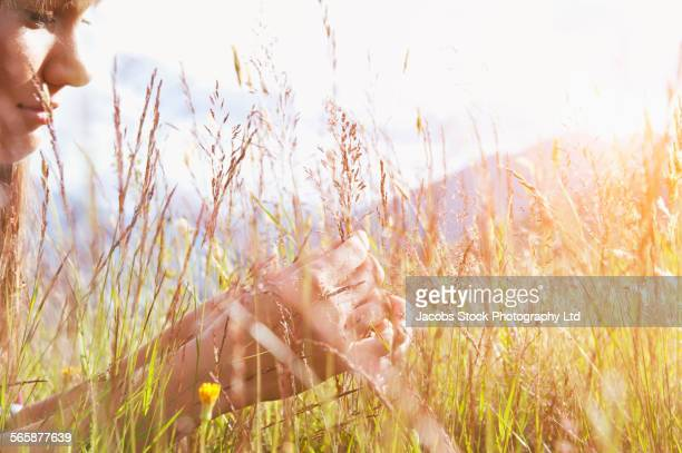 Pacific Islander woman laying in grass field,