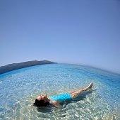 Pacific Islander woman laying in ocean