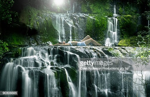 Pacific Islander woman laying in pool near waterfall : Foto de stock