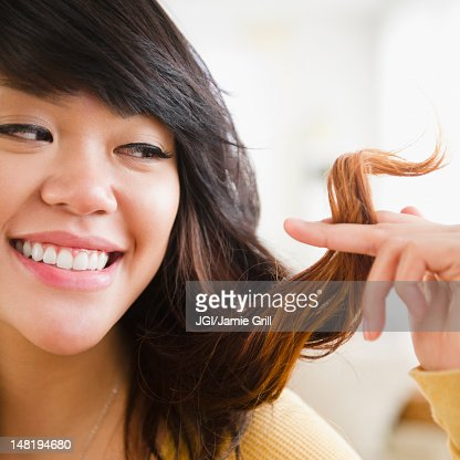 Pacific Islander woman looking at her hair