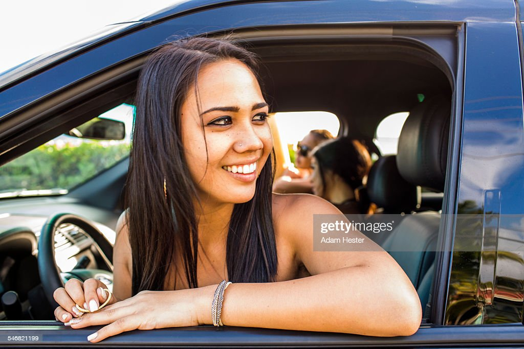 pacific islander woman looking out car window stock photo