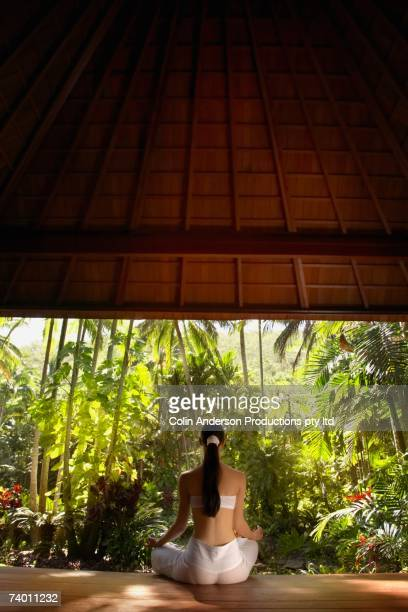 Pacific Islander woman meditating in jungle