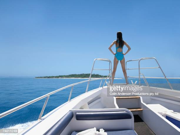 Pacific Islander woman on bow of yacht