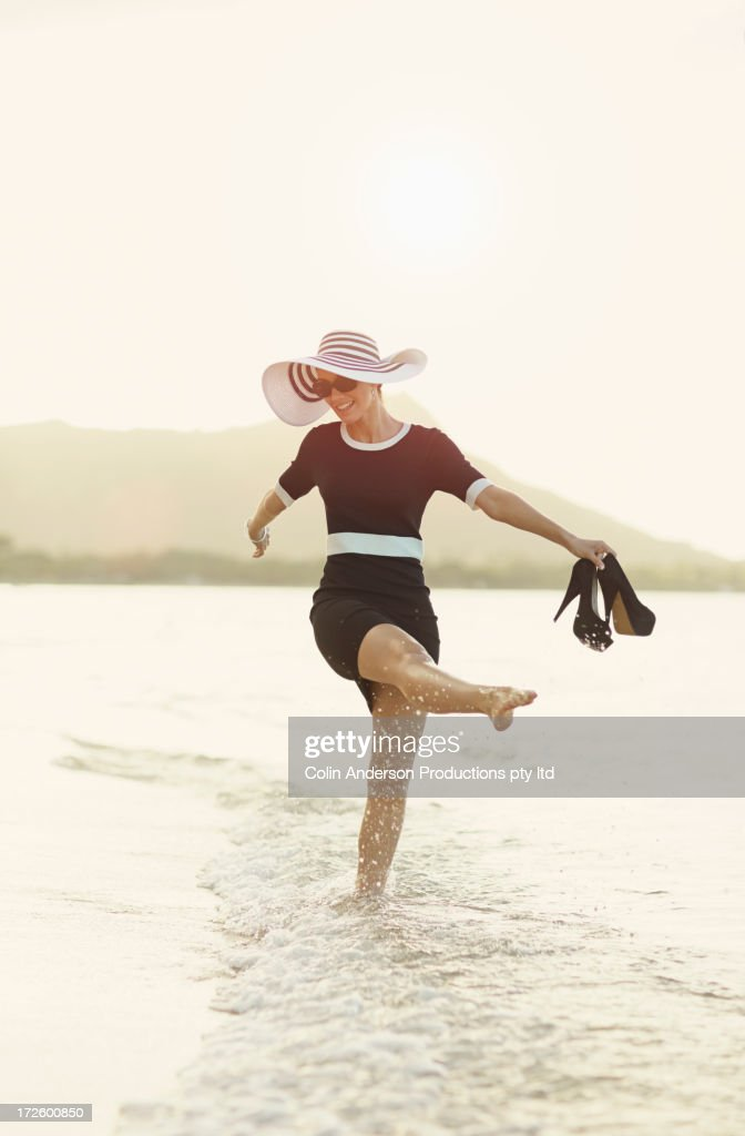 Pacific Islander woman playing in waves on beach : Stock Photo