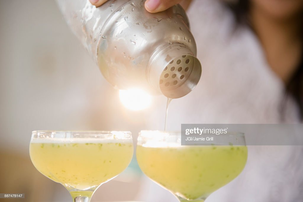 Pacific Islander woman pouring cocktails from shaker