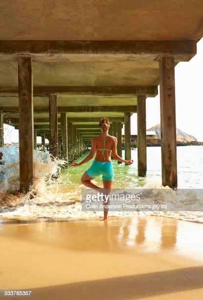 Pacific Islander woman practicing yoga under wooden pier on beach