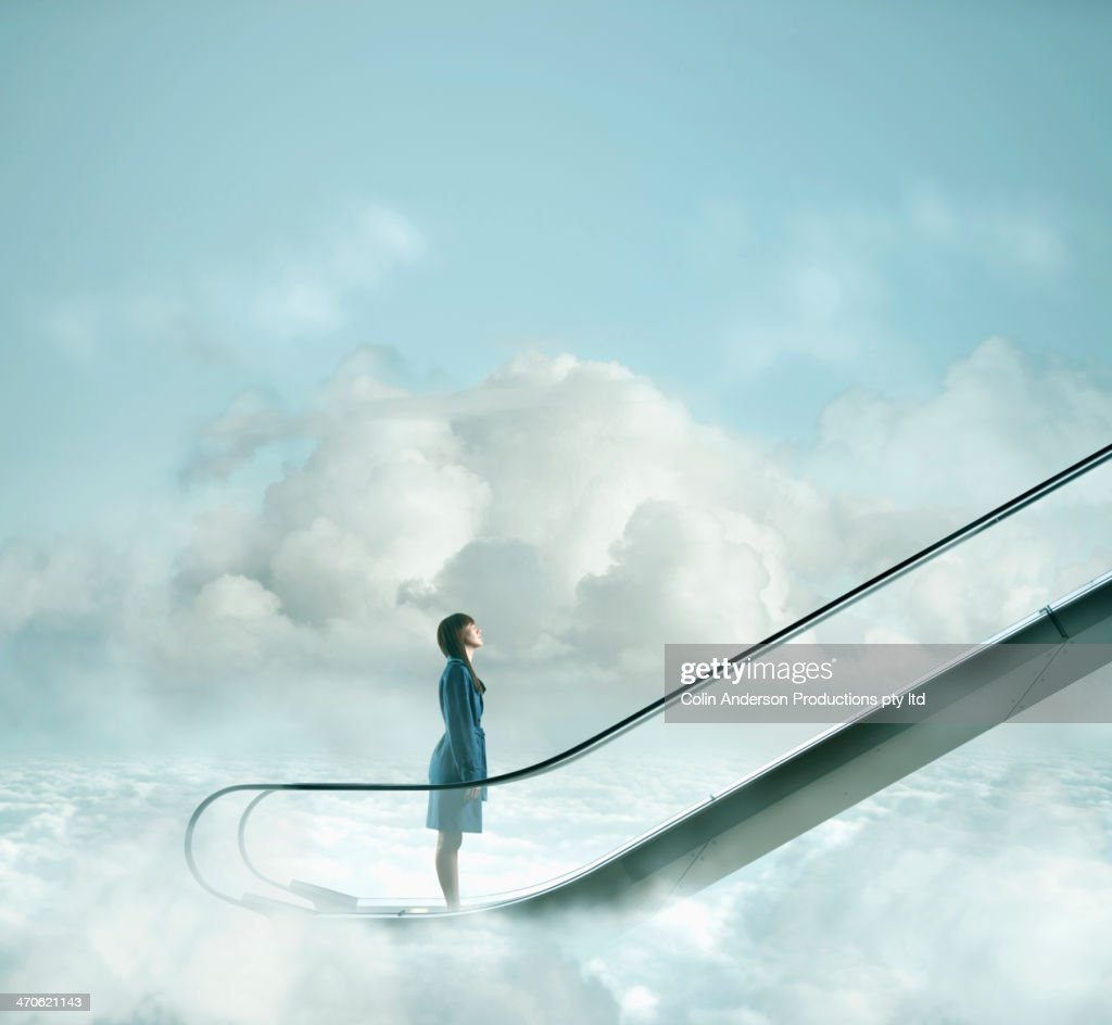 Pacific Islander woman riding escalator in sky