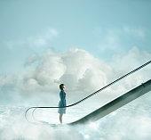 Pacific Islander woman riding escalator in sky