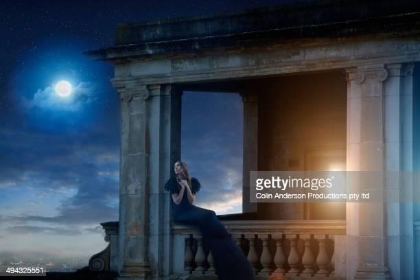 Pacific Islander woman sitting on ornate balcony
