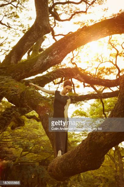 Pacific Islander woman standing in banyan tree