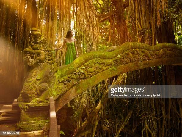 Pacific Islander woman standing on ornate ruins bridge