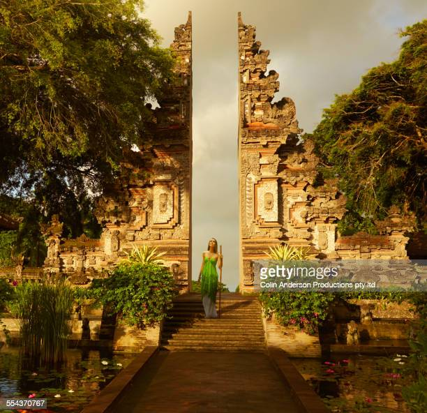 Pacific Islander woman standing on staircase of ornate ruins