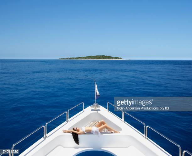 Pacific Islander woman sunbathing on bow of yacht