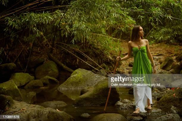 Pacific Islander woman walking in rocky creek