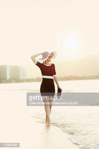 Pacific Islander woman walking in waves on beach