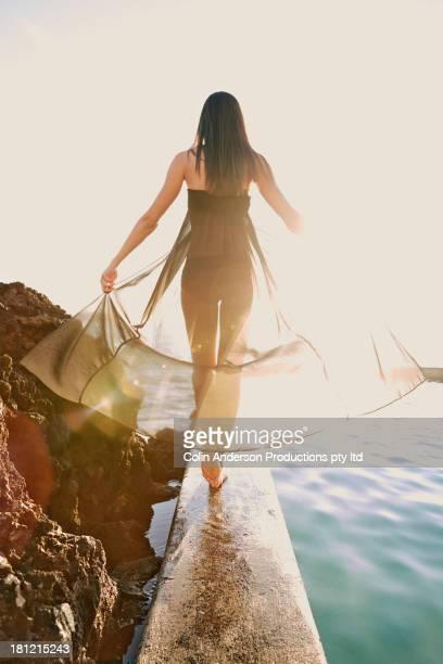 Pacific Islander woman walking on wooden railing