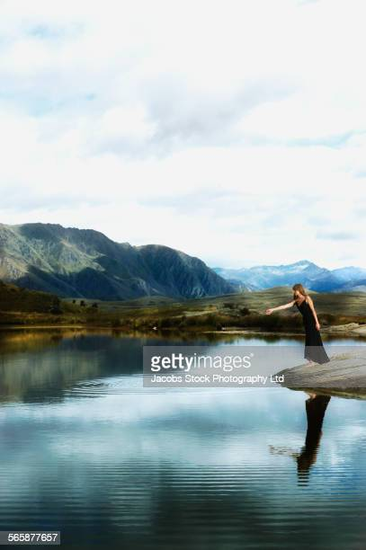 Pacific Islander woman wearing evening gown near remote lake