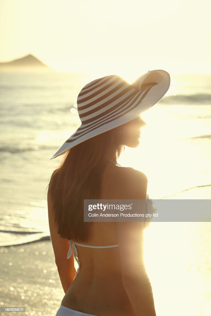 Pacific Islander woman wearing sun hat on beach