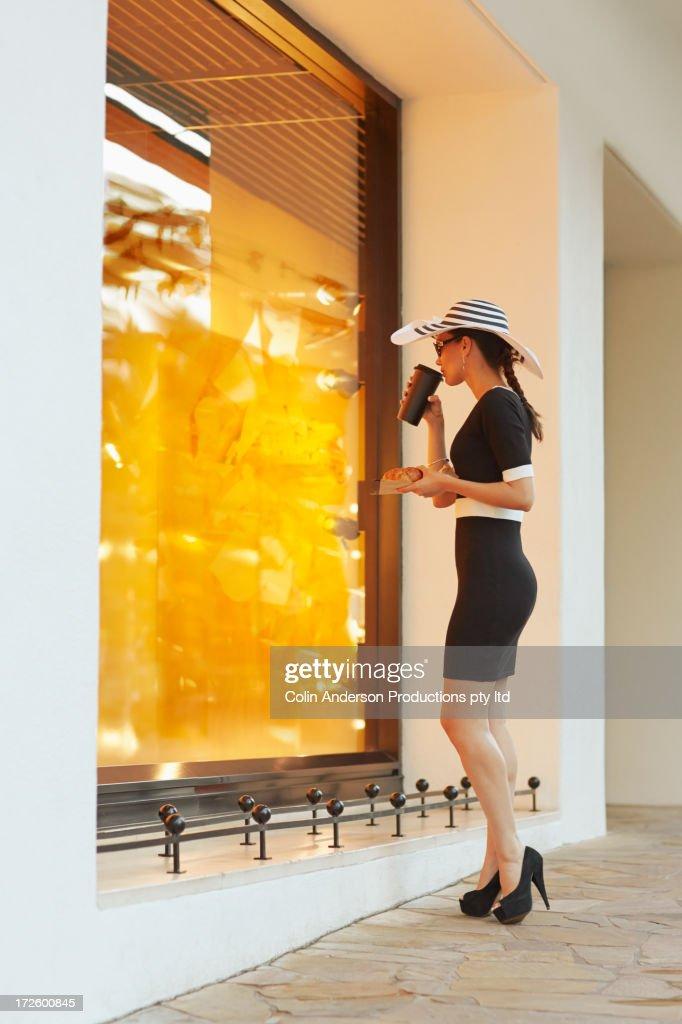 Pacific Islander woman window shopping on city street : Stock Photo
