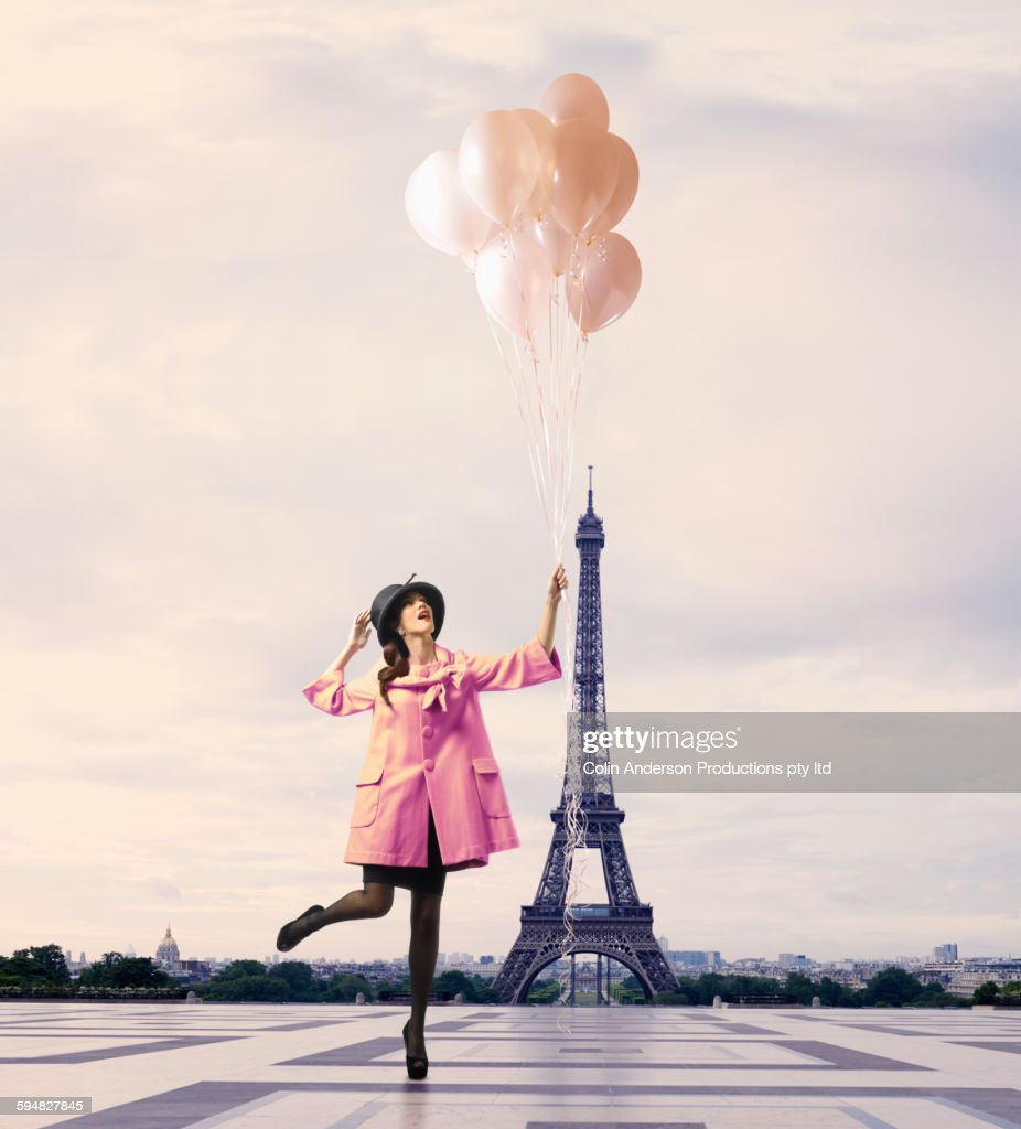Pacific Islander woman with balloons near Eiffel Tower, Paris, Ile