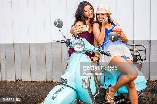 Pacific Islander women taking cell phone photograph on scooter
