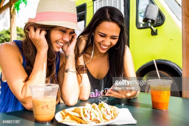 Pacific Islander women using cell phone near food cart