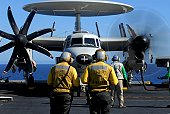 Flight deck directors watch as pilots of an E-2C Hawkeye assigned to the Golden Hawks start-up their engines in preparation for flight operations from the flight deck aboard the Nimitz-class aircraft