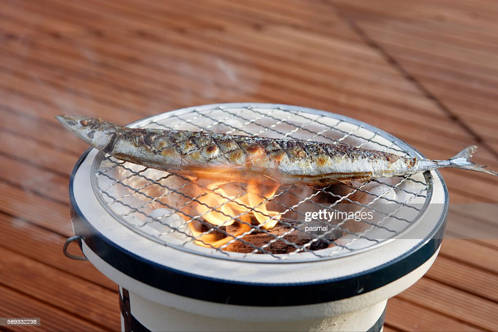 Pacific saury grilling on a charcoal brazier