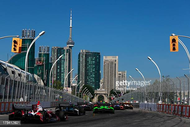 A pack of cars race down the straight away during the IZOD INDYCAR Series Honda Indy Toronto Race on July 13 2013 in Toronto Canada