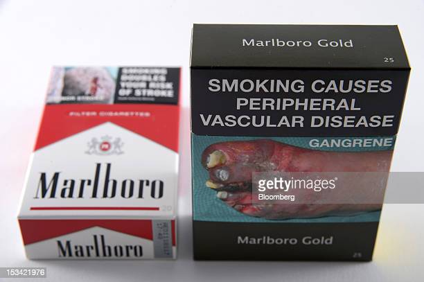 A pack of Philip Morris International Inc Marlboro Gold cigarettes in the new packaging right and Marlboro Red cigarettes in the old packaging are...