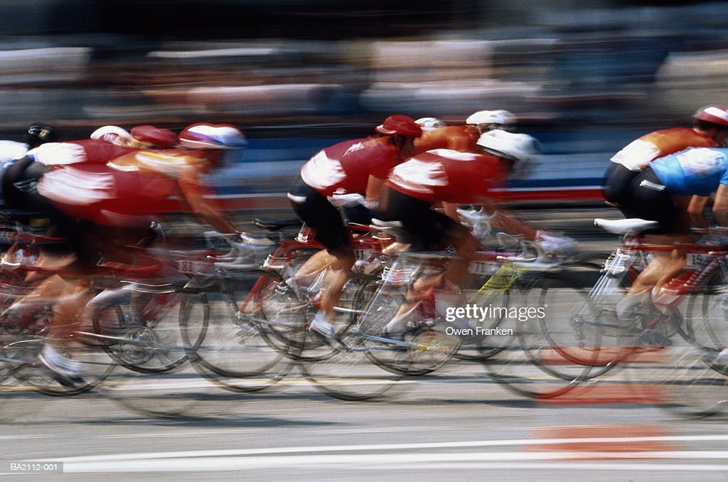 Pack of racing cyclists sprinting to finish,side view,blurred action