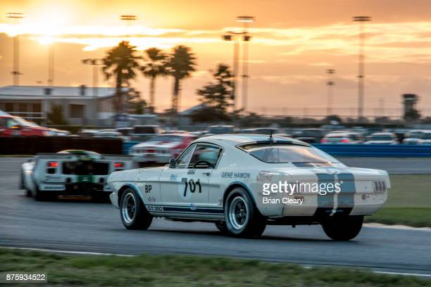 A pack of vintage race cars races on the track at night during the Classic 24 at Daytona Historic Sportscar Race at Daytona International Speedway on...