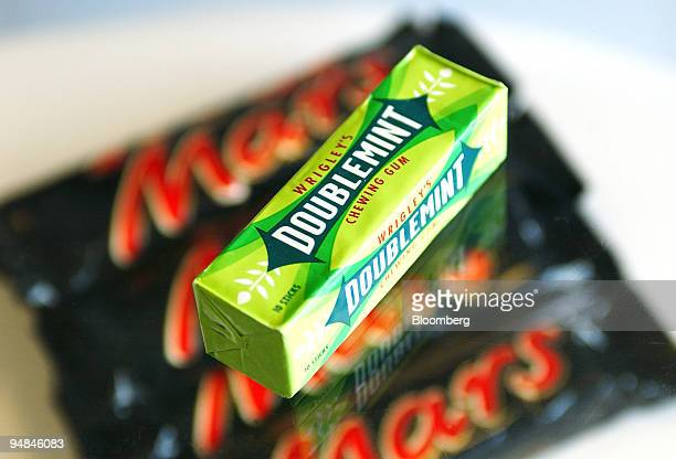 A pack of Wrigley's Doublemint chewing gum is displayed against a backdrop of Mars bars in this studio image in London UK on Monday April 28 2008...