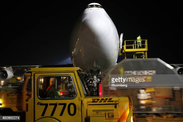 Package containers are moved past a Kalitta Air LLC 747 cargo jet at the DHL Worldwide Express hub of Cincinnati/Northern Kentucky International...