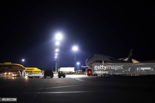 Package containers move past a Kalitta Air LLC 747 cargo jet at the DHL Worldwide Express hub of Cincinnati/Northern Kentucky International Airport...