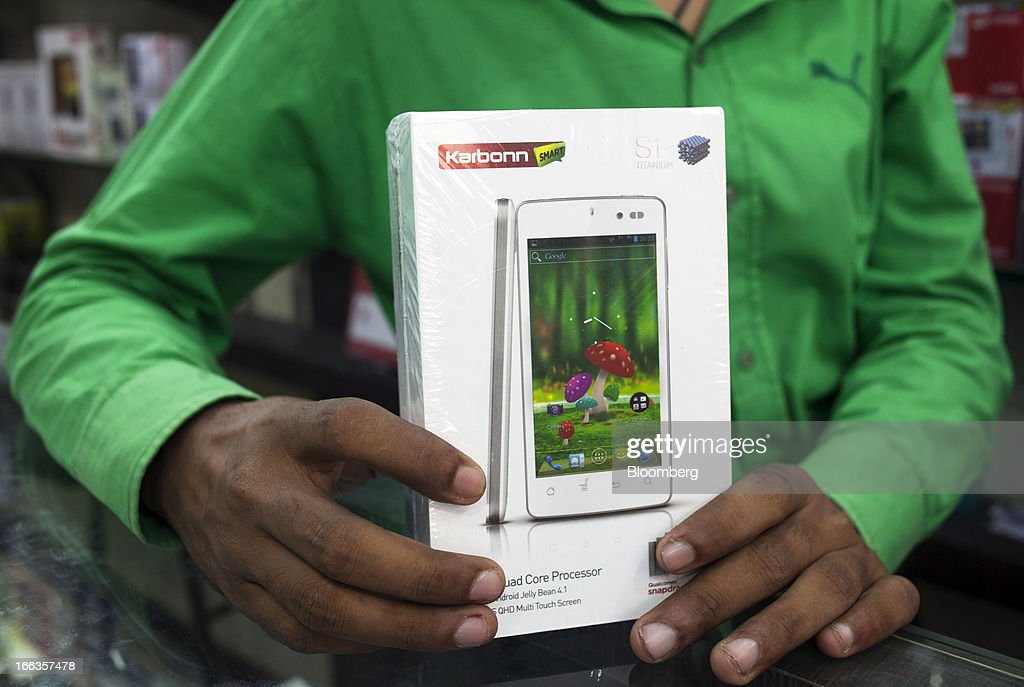 A packaged Karbonn Mobiles India Pvt. Ltd. S1 Titanium smartphone is held for a photograph by an employee at a wholesale smartphone outlet at Gaffar Market in New Delhi, India, on Tuesday, April 9, 2013. Apple Inc. and Samsung Electronics Co. are being outpaced in the fast-growing Indian smartphone market by aggressive local competitors Karbonn and Micromax Informatics Ltd. Photographer: Prashanth Vishwanathan/Bloomberg via Getty Images