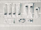 Packaged syringes and medical supplies, laid out on paper, ready for patient's use