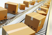 Cardboard boxes on conveyor belt in warehouse