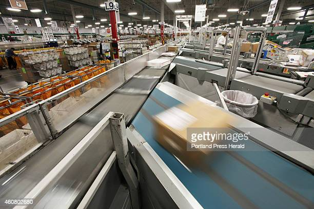 Packages move along a conveyor belt as they are sorted Thursday Dec 18 2014 at the USPS sorting facility in Scarborough Maine
