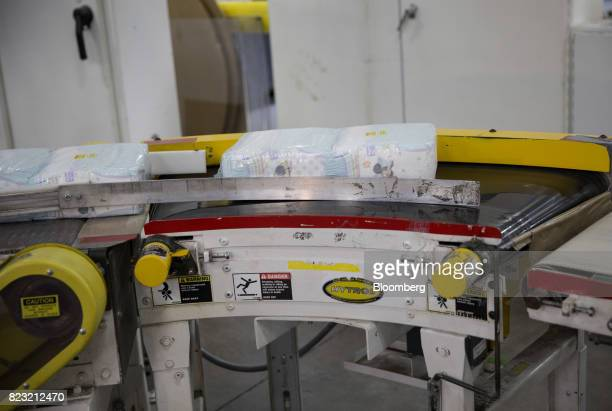 Packages of Huggies brand diapers move along a conveyor belt at the KimberlyClark Corp manufacturing facility in Paris Texas US on Tuesday Oct 27...