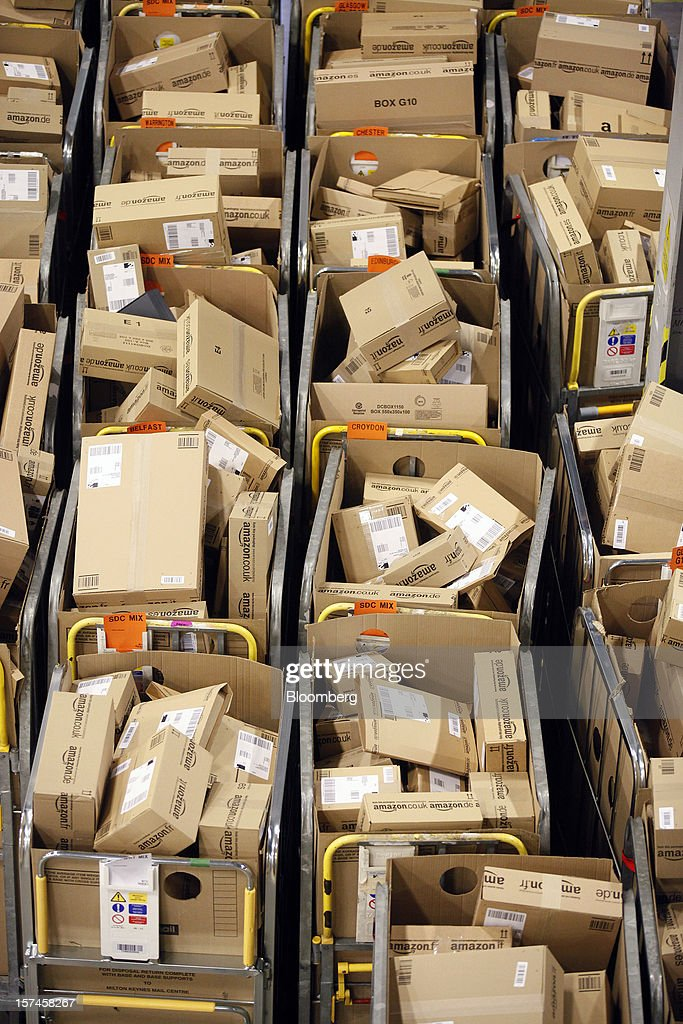 Packages sit in regional delivery dividers ahead of distribution at the Amazon.co.uk Marston Gate 'Fulfillment Center,' the U.K. site of Amazon.com Inc. in Ridgmont, U.K., on Monday, Dec. 3, 2012. U.K. consumer confidence unexpectedly increased to an 18-month high in November as Britons become more optimistic about the economy and their finances, GfK NOP Ltd. said. Photographer: Simon Dawson/Bloomberg via Getty Images
