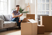 Packed cardboard boxes with young man sitting on sofa in living room calling delivery service at background, belongings in carton containers waiting for moving in out new home or relocation concept