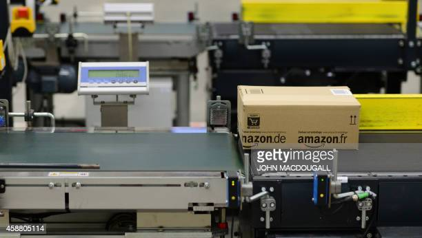 Packed goods for shipment make their way down a conveyor belt at US online retail giant Amazon's Brieselang logistics center west of Berlin on...