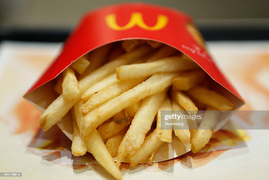A packet of french fries sit on a tray in this arranged photograph at a McDonald's restaurant operated by McDonald's Holdings Co Japan Ltd in Tokyo...