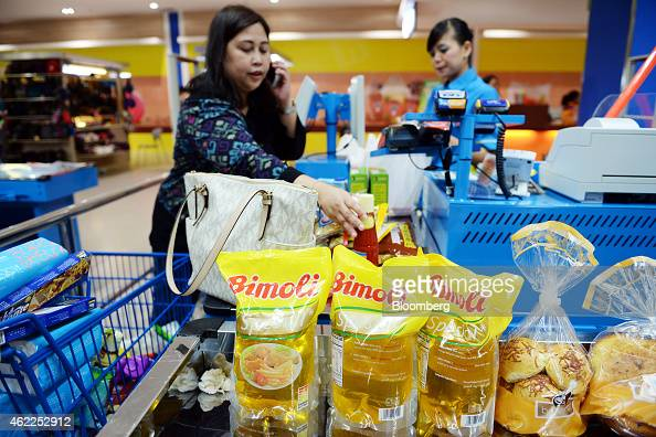 Packets of Bimoli cooking oil produced by PT Indofood Suskes Malmur Tbk and bread rolls sit at a checkout counter as a customer talks on a mobile...