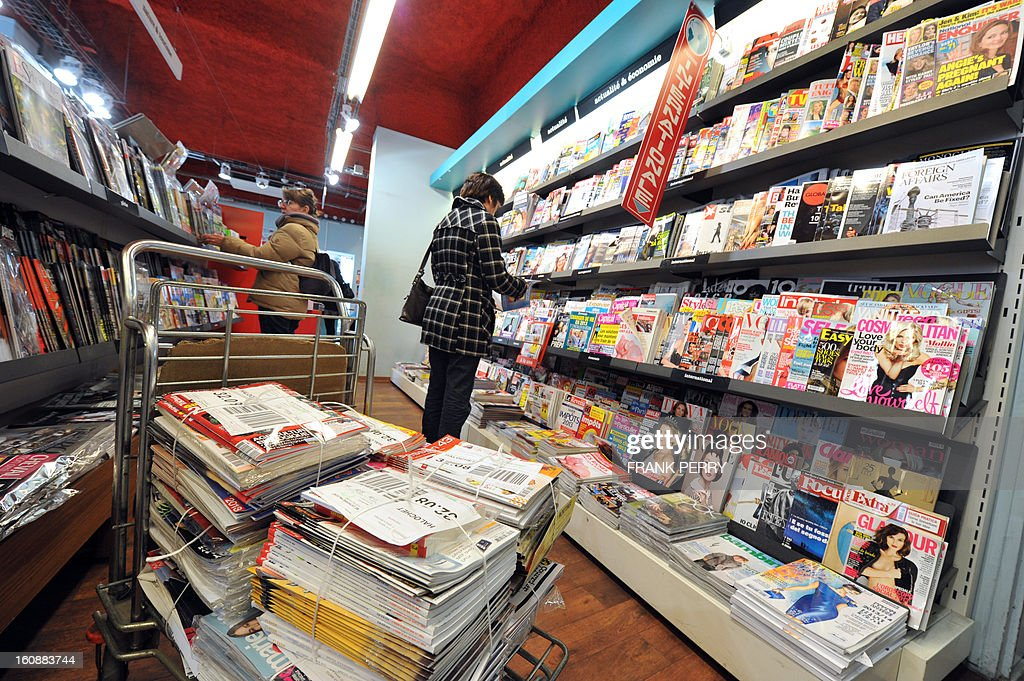 Packs of newspapers are pictured as clients look at magazines on the shelves of a bookshop on February 7, 2013 in Nantes, western France. AFP PHOTO FRANK PERRY