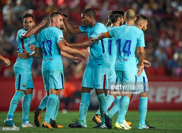 Paco Alcacer of Barcelona celebrates with his teammates after scoring a goal during the preseason friendly match between Gimnastic de Tarragona and...